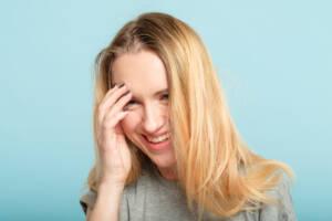 blonde Frau fasst sich lachend ins Gesicht Face Palm