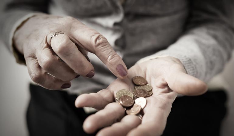 Ältere Hand in der Kleingeld liegt