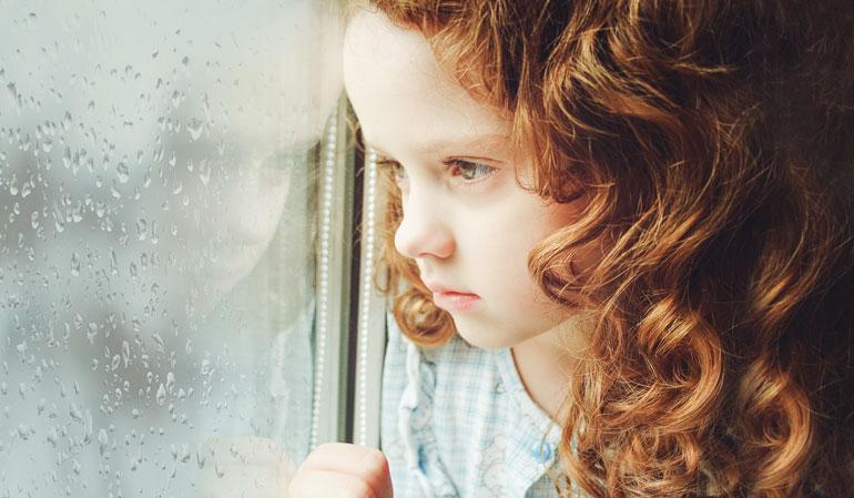 Trauriges Kind schaut aus Fenster