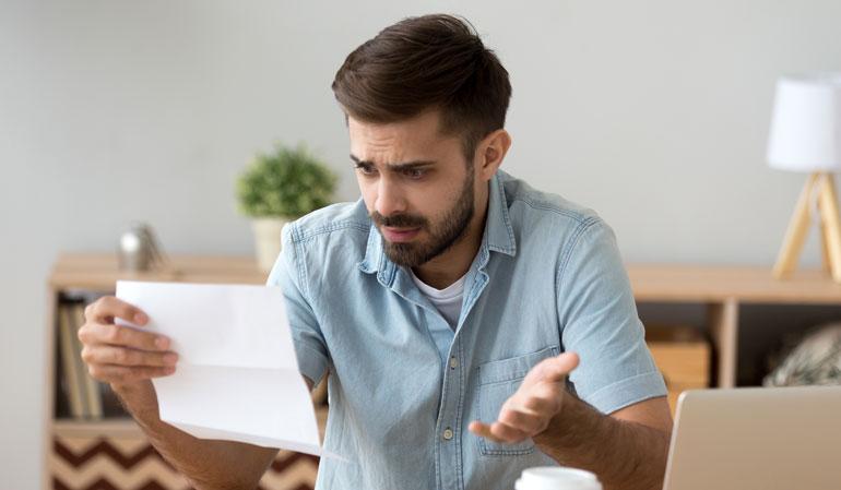 Mann hält Brief in der Hand und ist schockiert