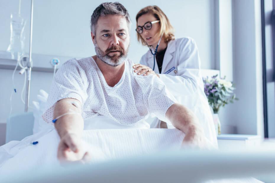 Mann liegt im Krankenhausbett und wird von Ärztin untersucht