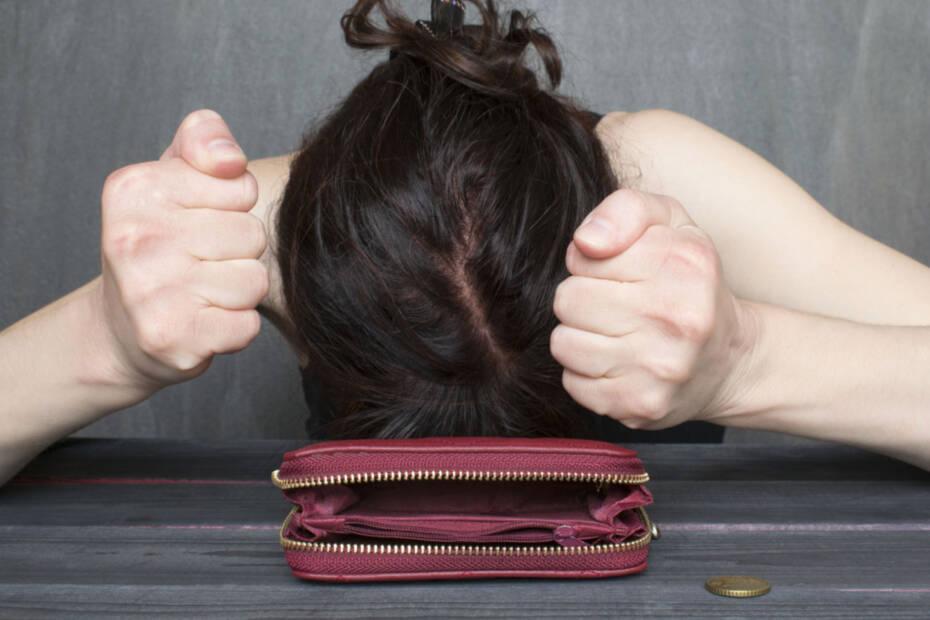 Verzweifelte Frau mit Geldbörse