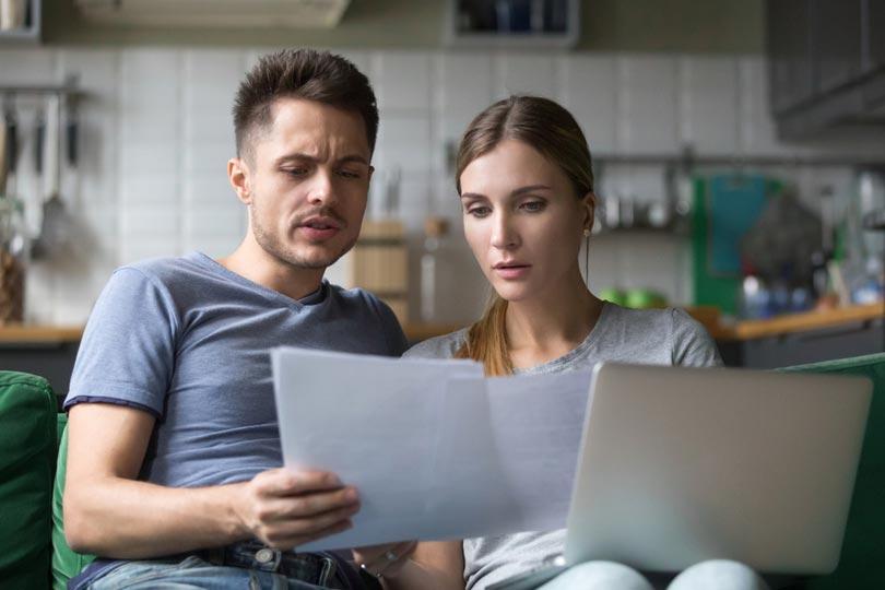 Verwirrtes Paar bei Durchsicht der Rechnungen