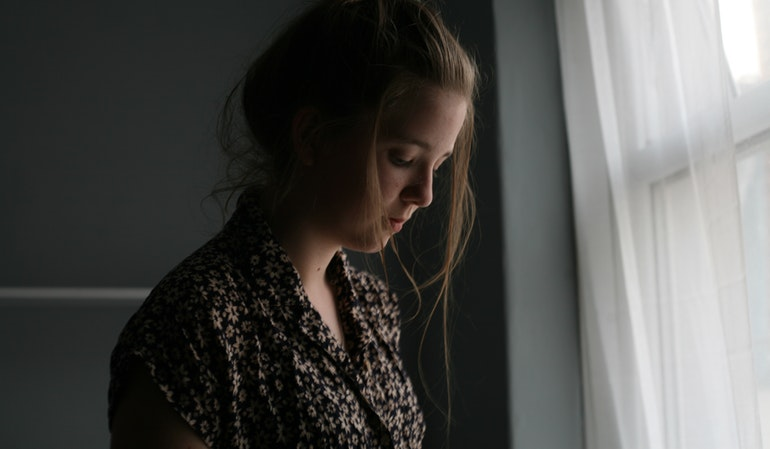 Traurige Frau steht neben Fenster