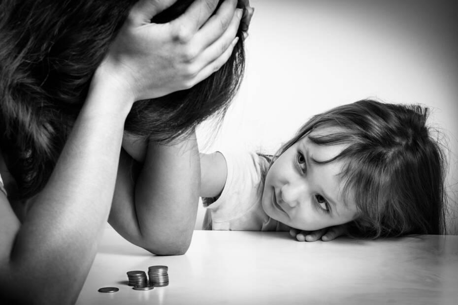 Kleine Familie. Alleinerziehende Mutter hat finanzielle Probleme. Ihre kleine Tochter beruhigt traurige Mutter.