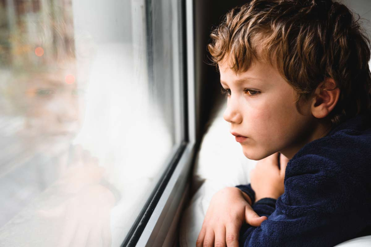 Trauriger Junge schaut aus Fenster