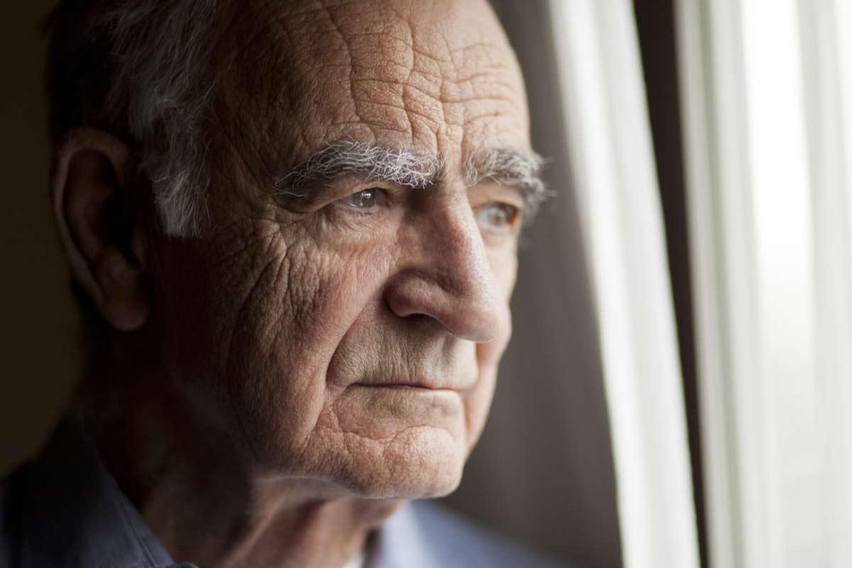 Alter Mann schaut nachdenklich aus dem Fenster