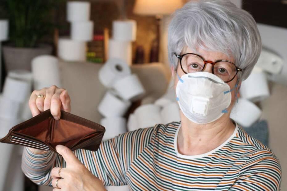 Ältere Frau mit Gesichtsmaske hält leeres Portemonnaie hoch