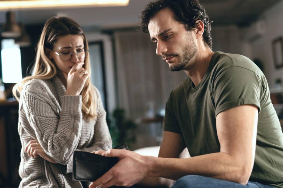 Hartz IV Paar sitzt frustriert mit leerem Portemonnaie auf Sofa