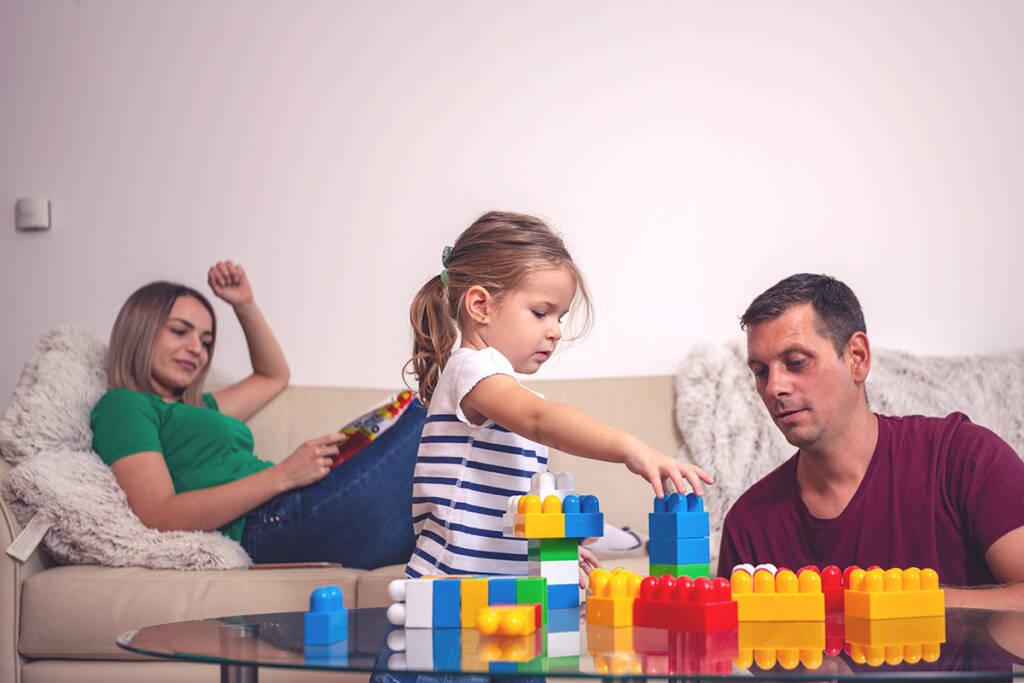 Mutter, Vater und Tochter spielen im Wohnzimmer