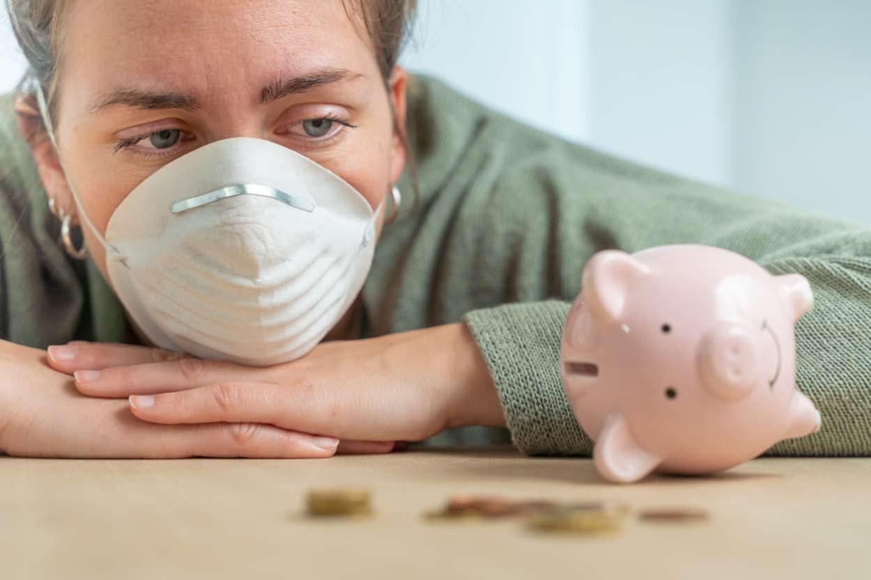 Traurige Frau mit Gesichtsmaske sitzt vor leerem Sparschwein