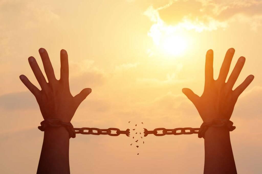 Hände in zerbrochenen Handschellen
