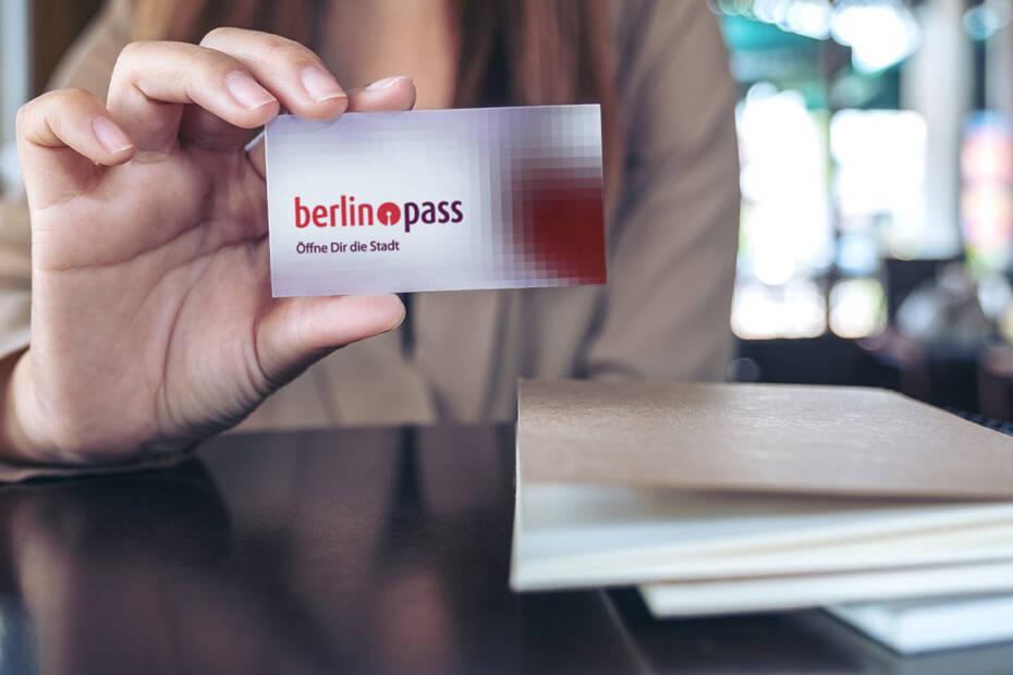 junge Frau mit Berlinpass in der Hand