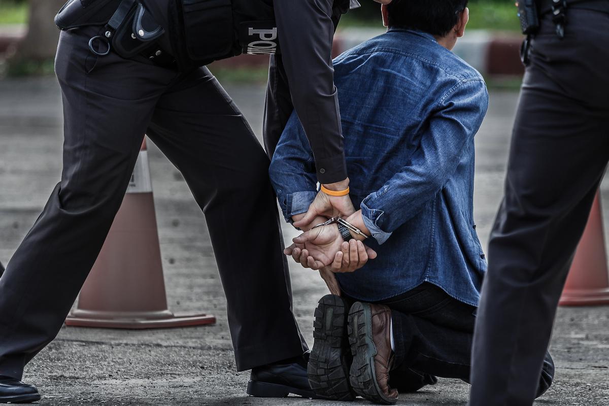 Mann in Handschellen mit 2 Polizisten