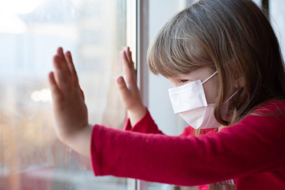 trauriges Kind guckt mit Corona Maske aus Fenster