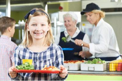 Mädchen mit warmen Mittagessen auf Tablett in Schulkantine