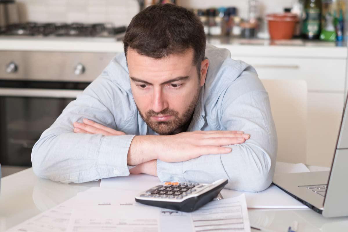 Mann sitzt frustriert über Rechnungen