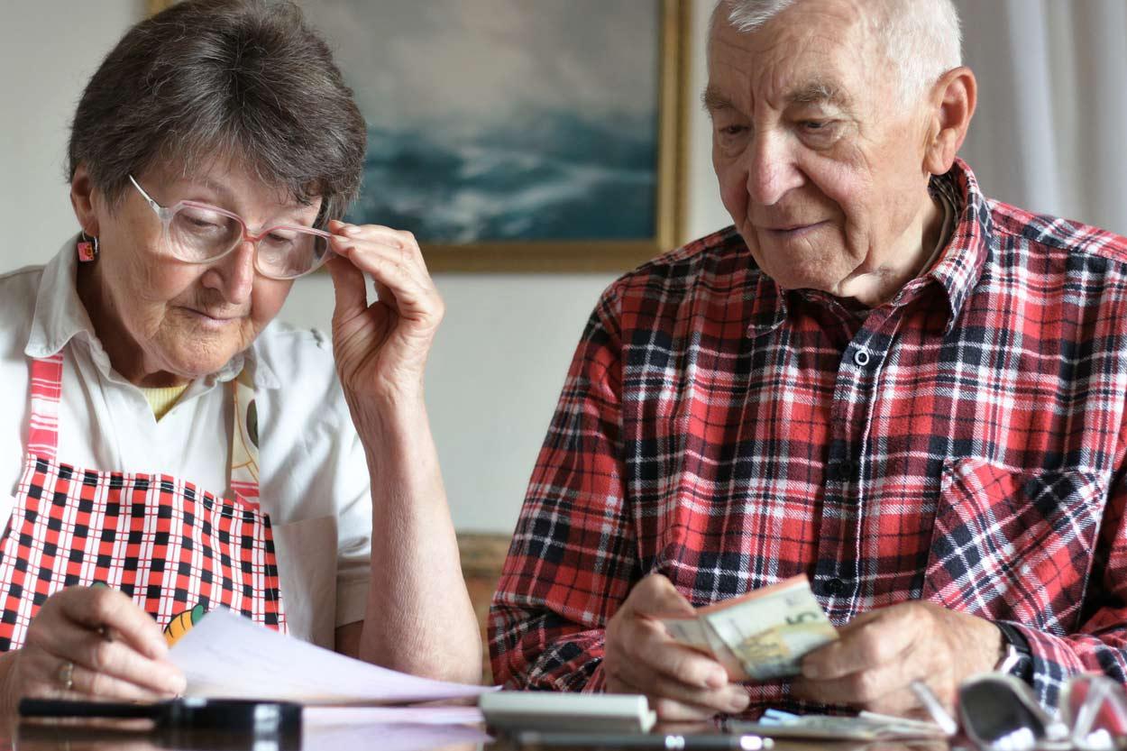 Älterer HErr und ältere Dame zählen Geld