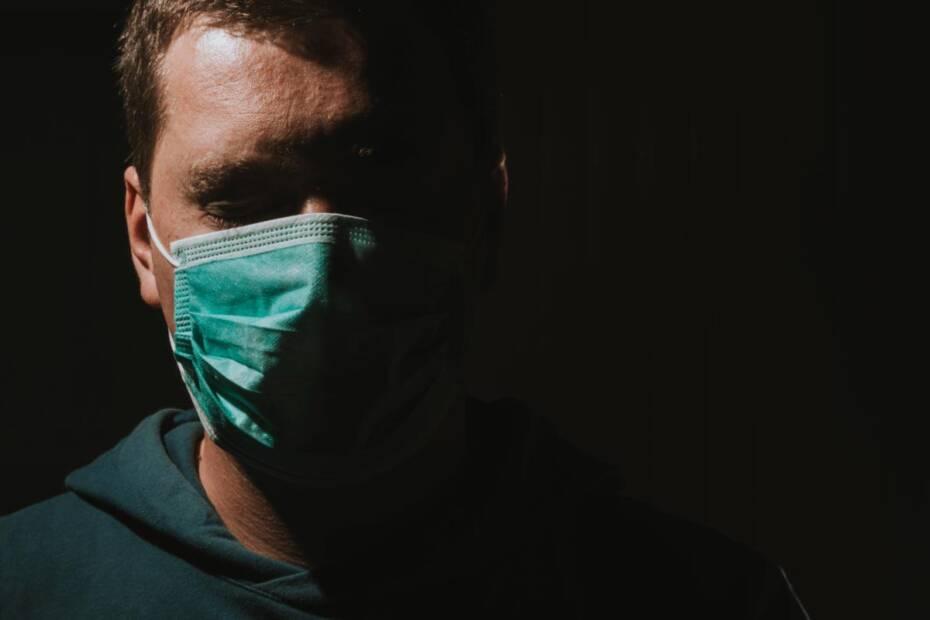Mann mit Corona-Mundschutz vor schwarzem Hintergrund