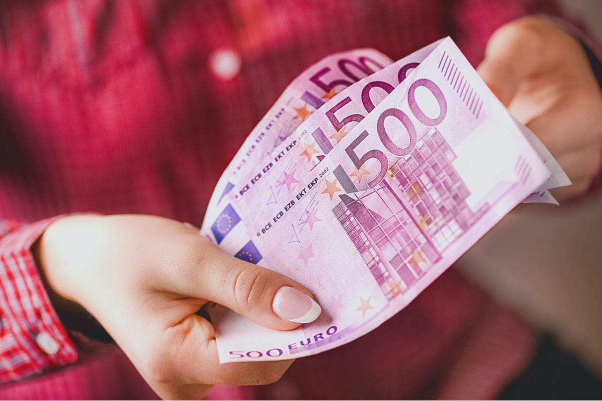 Frau hält 3 500 Euro Scheine in der Hand