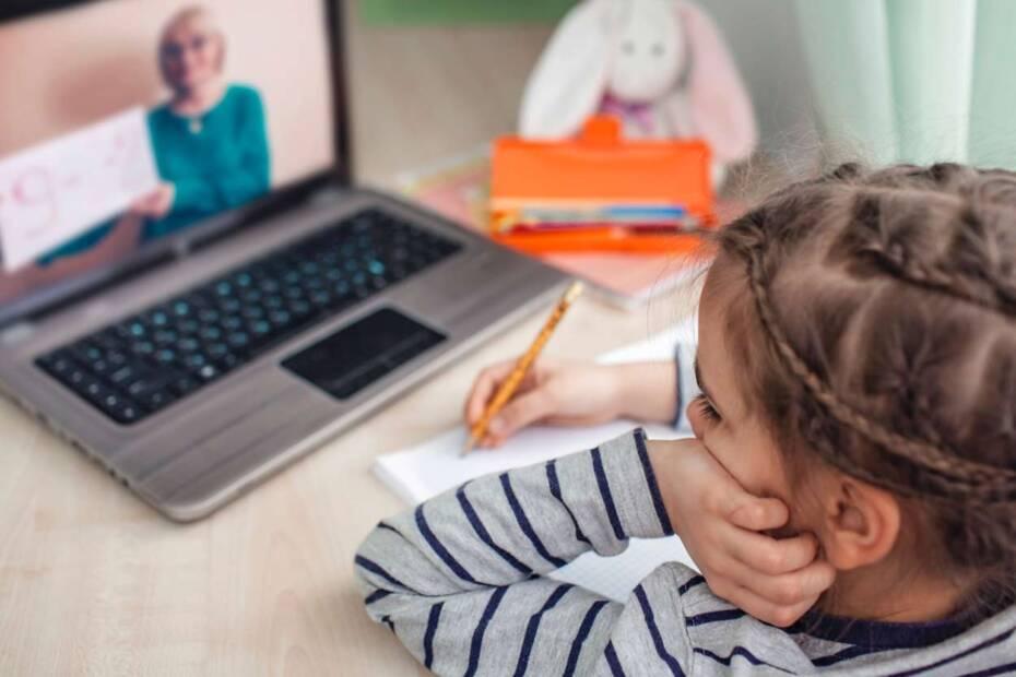Kleines Mädchen sitzt vor einem Laptop