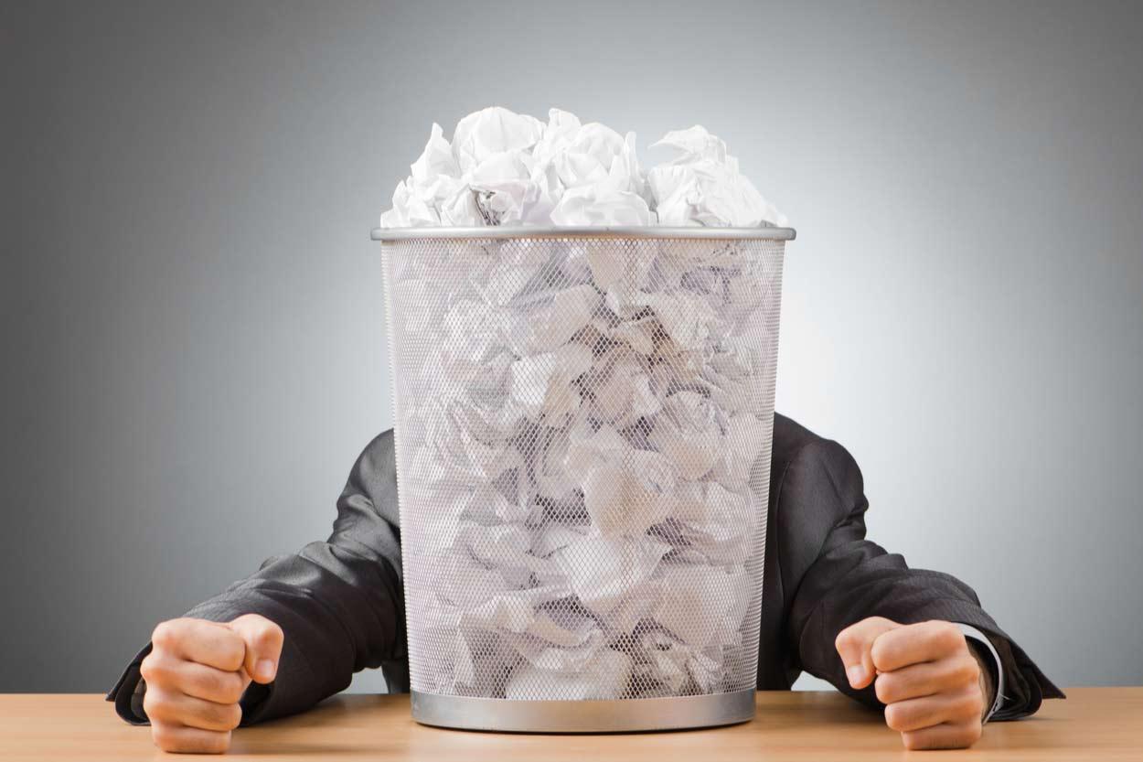 Mann sitzt vor vollem Papierkorb