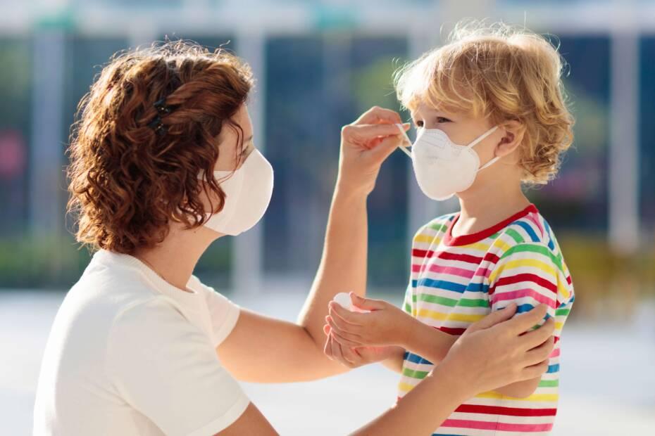 Mutter setzt Kind Schutzmaske auf