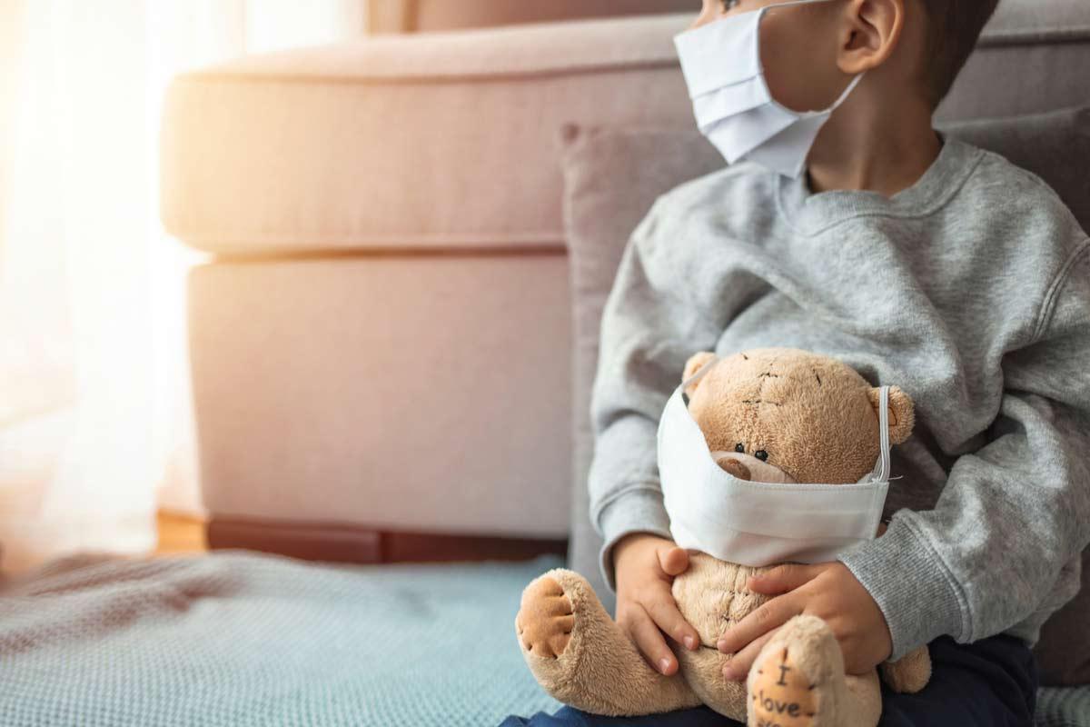 Junge mit Gesichtsmaske und Teddy