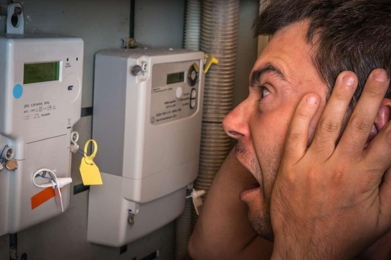 Mann steht entsetzt vor Stromzähler