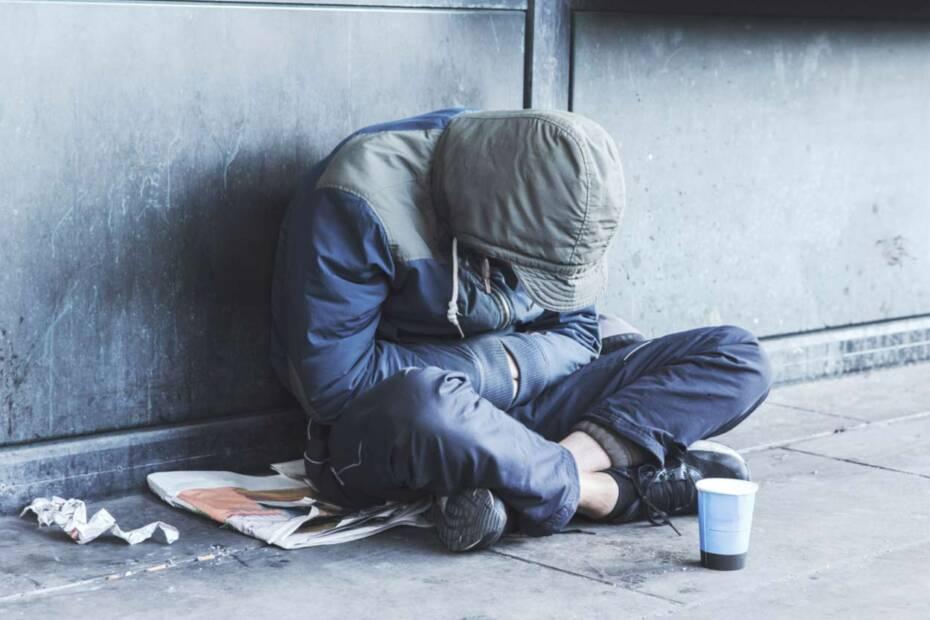 Obdachloser Mann sitzt auf der Straße