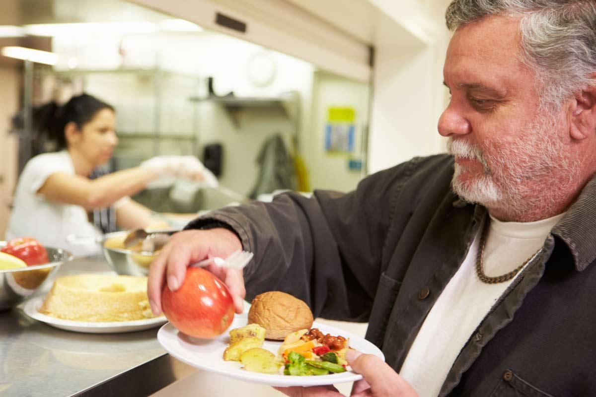 Mann erhält Essen bei Tafel