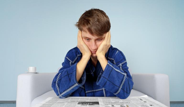 Trauriger Mann liest Zeitung