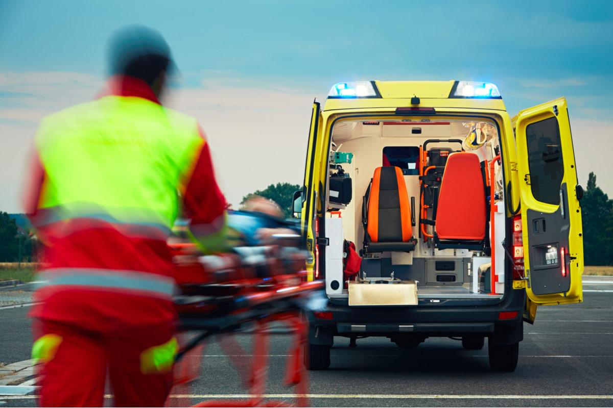 Sanitäter fährt mit Patient auf Trage zum Krankenwagen