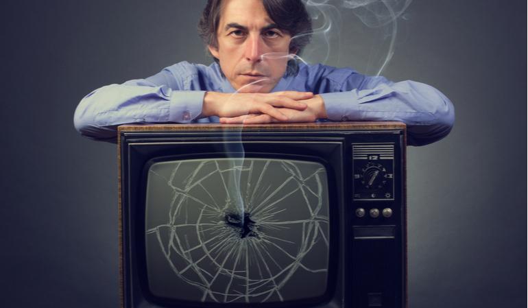 Ernster Mann steht über einem kaputten Fernseher