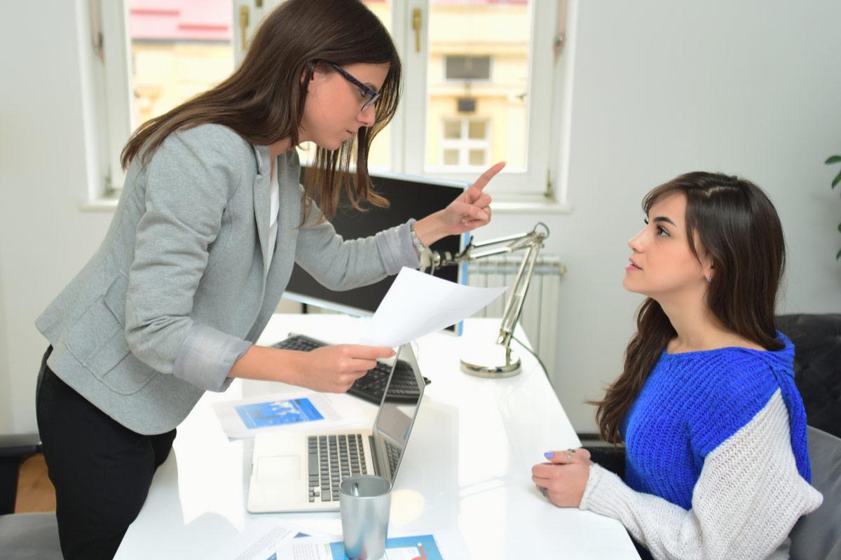 Frau steht mahnend hinterm Schreibtisch vor einer einngeschüchterten sitzenden Frau