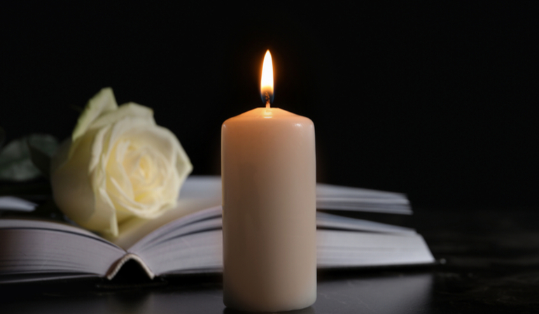 Brennende Kerze vor einem Buch mit einer weißen Blume