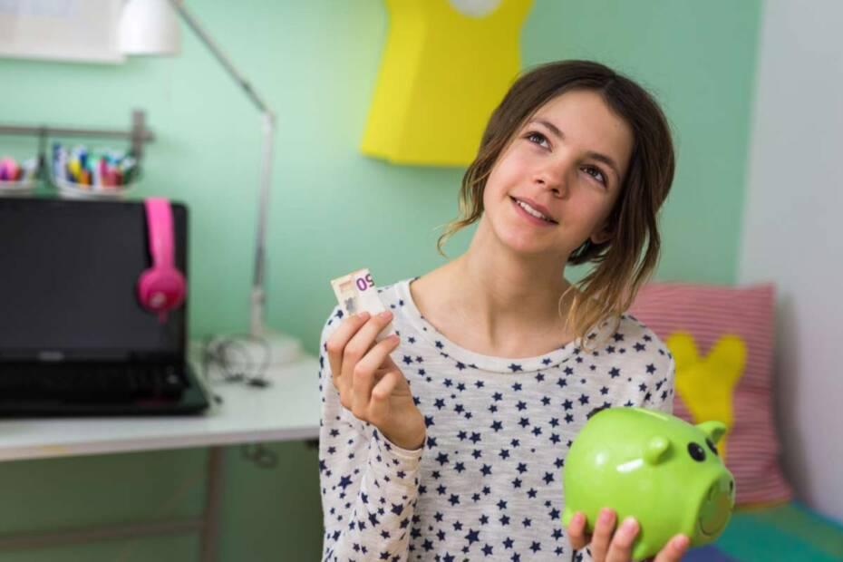 Mädchen steckt Geld in Sparschwein