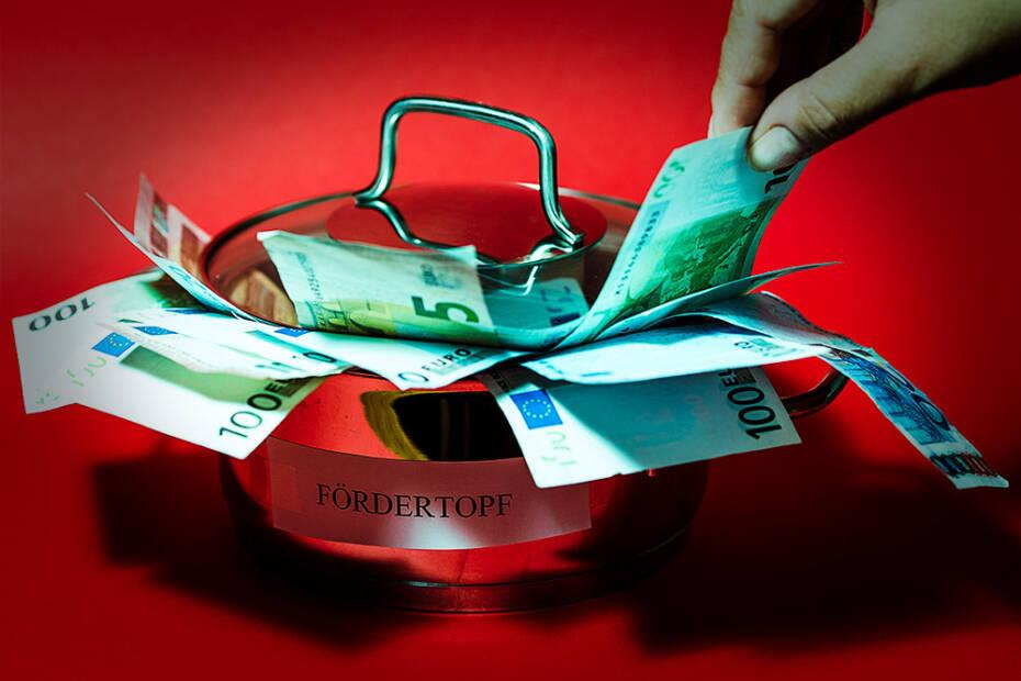 Topf mit Geldscheinen vor rotem Hintergrund