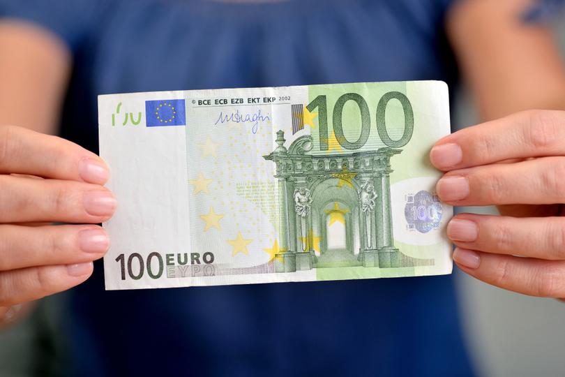 Frau im blauen T-Shirt hält 100 Euro Schein