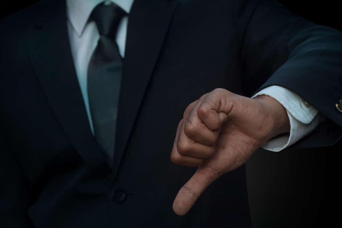 Mann im Anzug zeigt einen Daumen runter