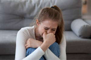 Verzweifelte Frau weint vor Sofa