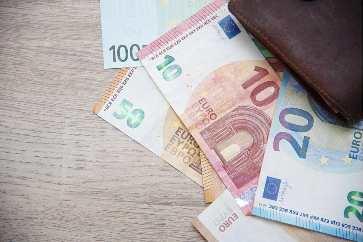 Geldscheine und Geldbörse auf Holztisch