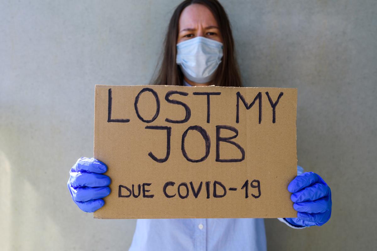 Frau hält ein Schild mit der Aufschrift Job verloren wegen Corona