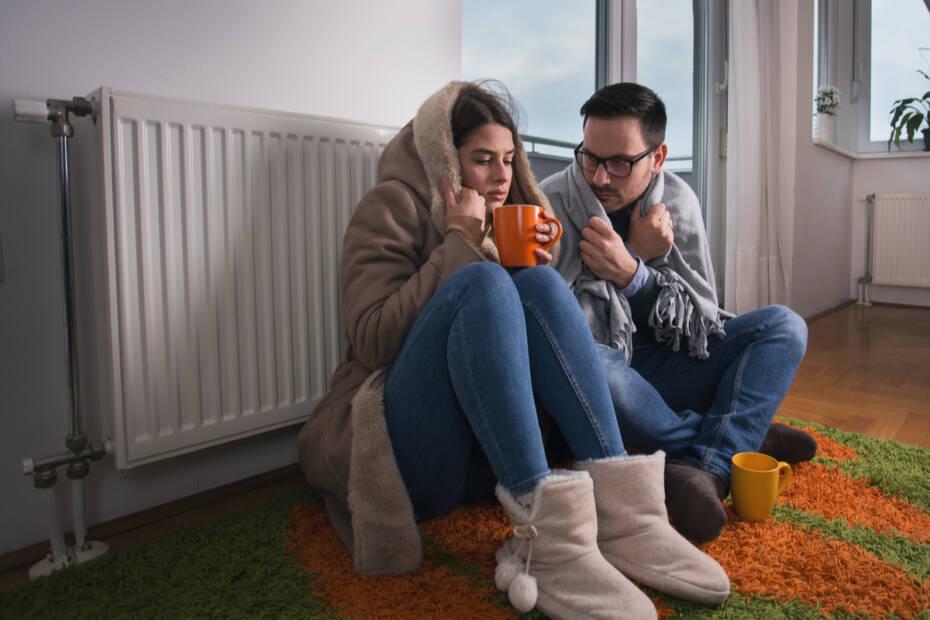 junges Paar sitzt dick zugedeckt vor Heizung