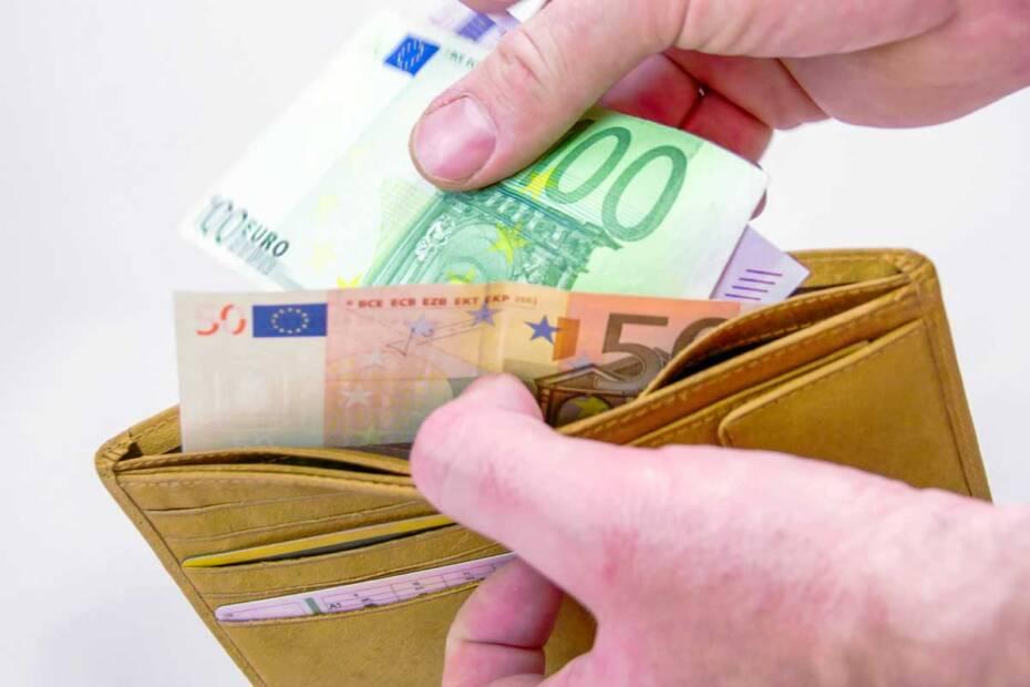 Hände greifen nach Geld in Geldbörse