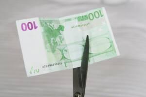 Geldschein 100 Euro mit Schere zerschneiden