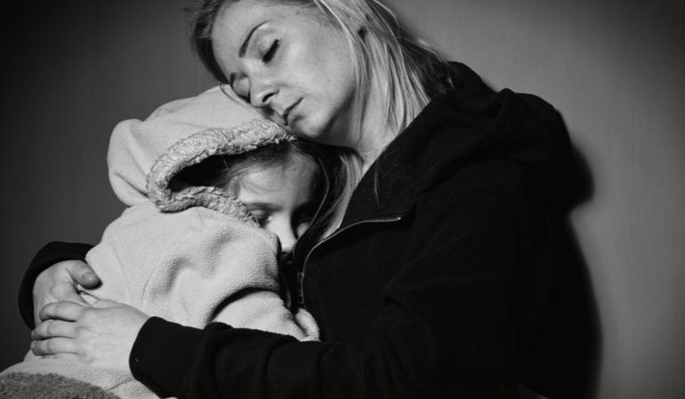 Alleinerziehende Mutter hält ihr Kind im Arm