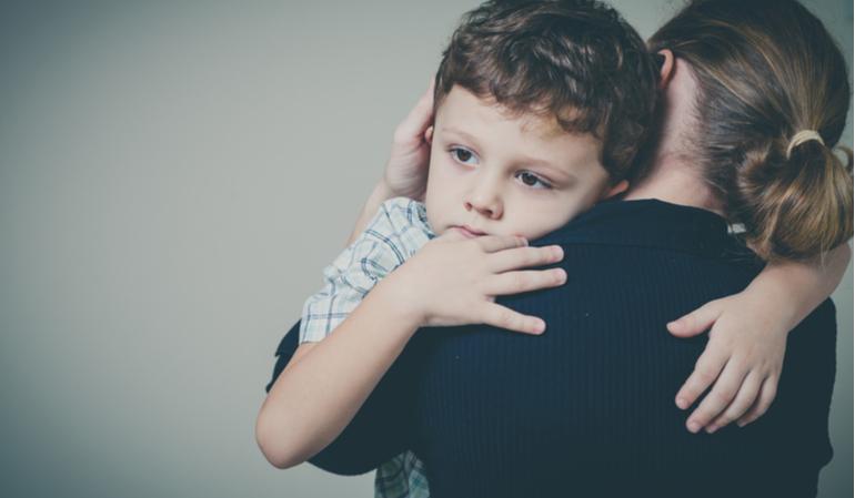 Trauriger Junge im Arm seiner Mutter