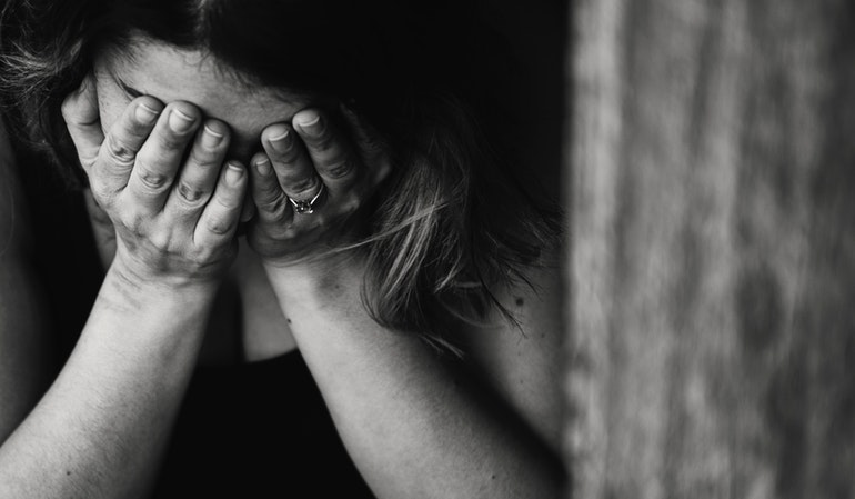 Traurige Frau vergränt das Gesicht in ihren Händen
