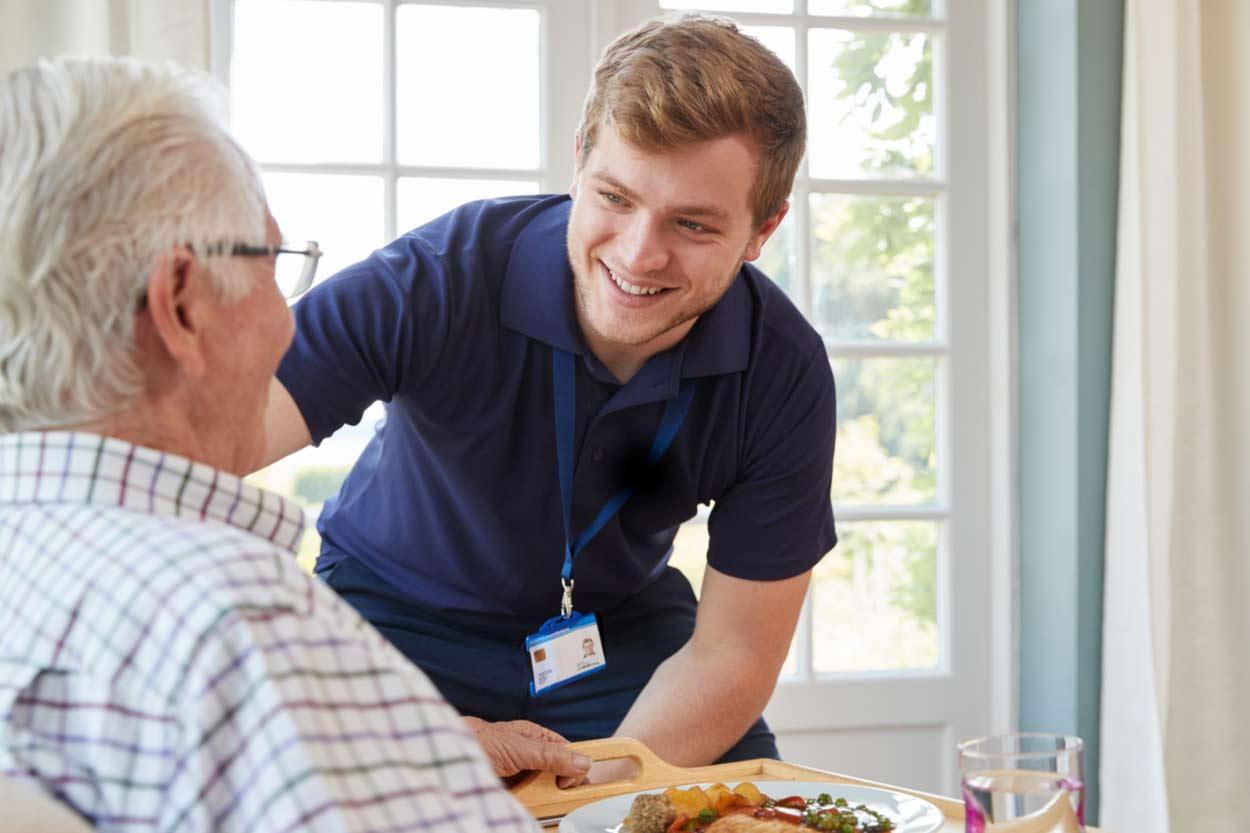 Altenpfleger kümmert sich um alten Mann
